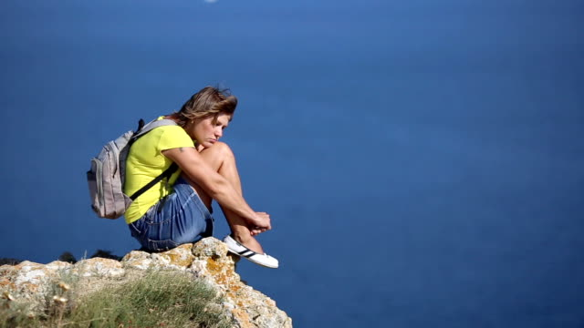 Young woman resting on a mountain coast
