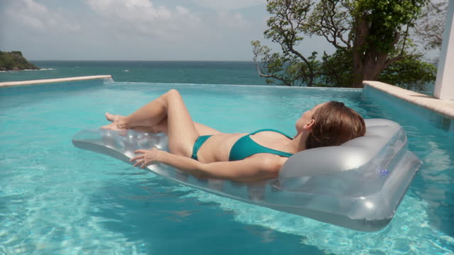 ms young woman resting on inflatable raft in infinity pool, floating slowly past camera/ scarborough, tobago, trinidad and tobago - inflatable raft stock videos and b-roll footage