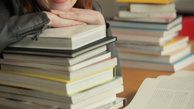 cu tu young woman resting on stack of books smiling - stapeln stock-videos und b-roll-filmmaterial