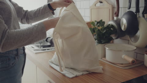 vídeos y material grabado en eventos de stock de joven mujer que regresa a casa de viaje de compras desembalaje bolsas de plástico gratis de comestibles - cocina estructura de edificio