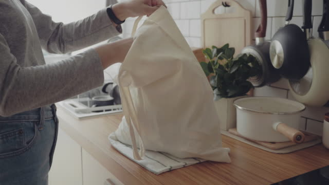 young woman returning home from shopping trip unpacking plastic free grocery bags - kitchen stock videos & royalty-free footage