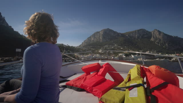 young woman rides a boat on the coast of capri in italy - mid length hair stock videos & royalty-free footage