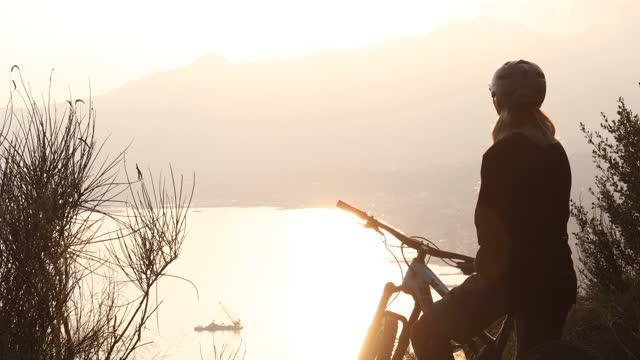 young woman rides mountain bike to viewpoint, above sea - ウォーターボトル点の映像素材/bロール