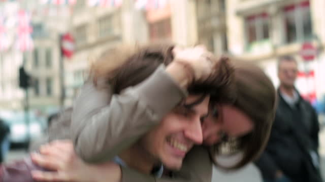 Young woman rides piggyback and ruffles her boyfriend‰Ûªs hair while crossing a London street.