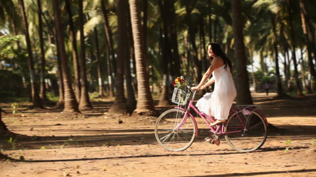 young woman riding a bicycle  - kleid stock-videos und b-roll-filmmaterial