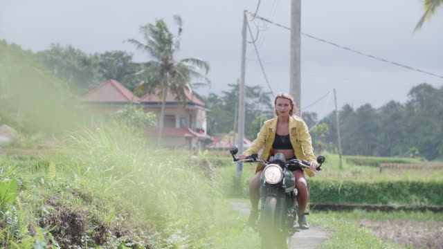 a young woman riding a motorcycle in exotic tropical bali, indonesia. - zen like stock videos & royalty-free footage