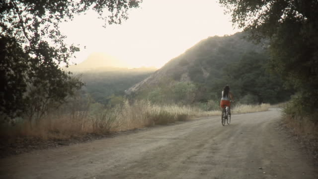 vidéos et rushes de ws young woman riding bike down dirt road / malibu creek, california, usa - colline