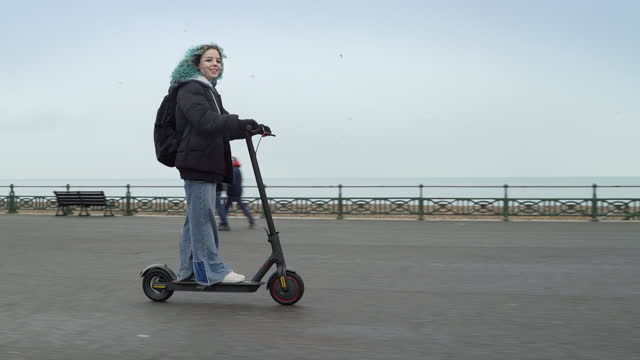 young woman riding electric scooter along seaside path - independence stock videos & royalty-free footage