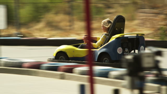 ws ts young woman riding go-cart, orem, utah, usa - go cart stock videos & royalty-free footage