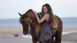 Young Woman Riding Horse On The Seashore