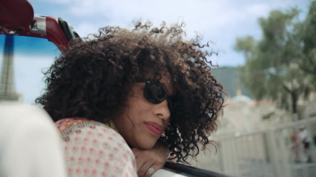 young woman riding in classic convertible smiles as she looks out at sunny las vegas. - curly hair stock videos & royalty-free footage