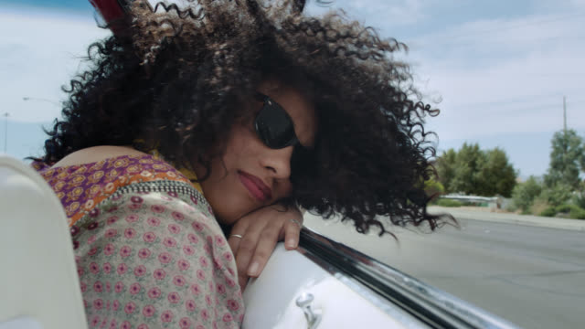 SLO MO. Young woman riding in classic convertible stares at camera as wind blows her hair.