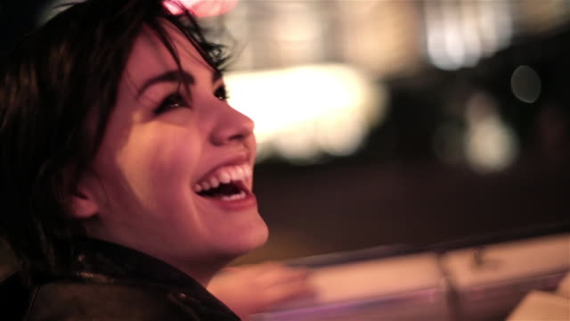 vidéos et rushes de young woman riding in classic convertible takes in the late night sights and sounds of the las vegas strip - aller tranquillement
