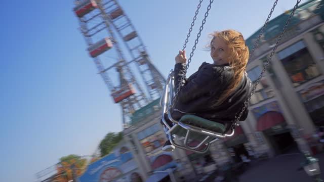 Ung kvinna rider på chairoplane
