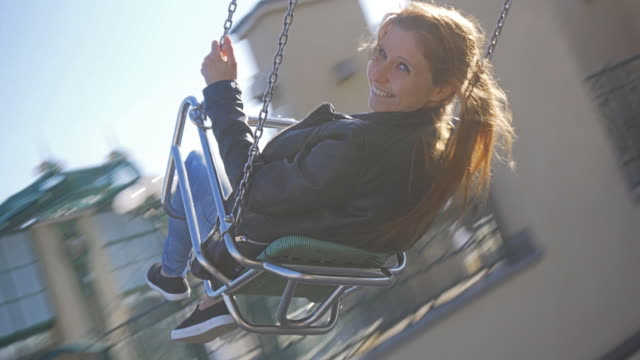 Young woman riding on chairoplane