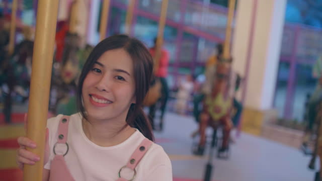 young woman riding on marry go round - school fete stock videos and b-roll footage