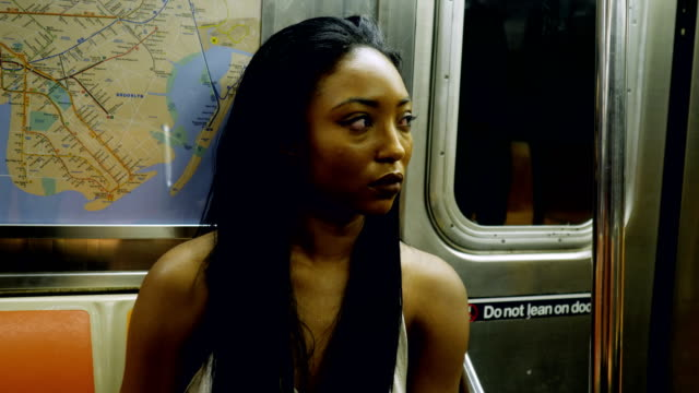 young woman riding the new york city subway - metropolitana di new york video stock e b–roll