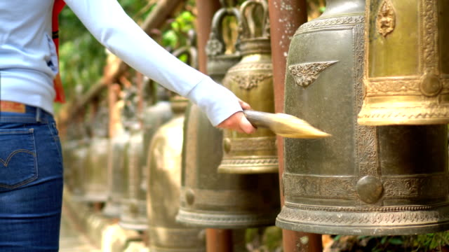 young woman ringing big bells for luck in thai temple - large stock videos & royalty-free footage