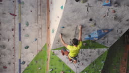 Young Woman Rock climber is Climbing At Inside climbing Gym. slim pretty Woman Exercising At Indoor Climbing Gym Wall.