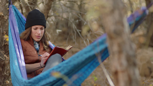Young woman rocks in forest hammock and writes in journal.