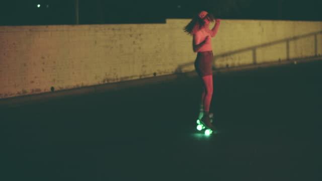 vídeos de stock e filmes b-roll de young woman roller skating at night - rodar