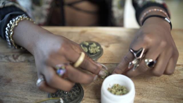 a young woman rolling a joint. - zerdrückt stock-videos und b-roll-filmmaterial