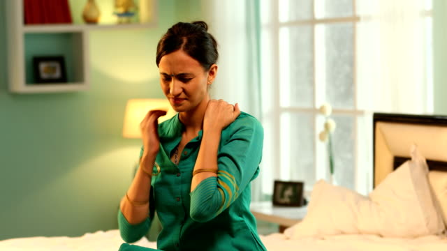 ms young woman rubbing her painful neck while sitting on bed / new delhi, delhi, india - neckache stock videos & royalty-free footage