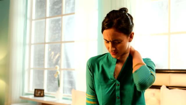vídeos de stock e filmes b-roll de ms young woman rubbing her painful neck while sitting on bed / new delhi, delhi, india - dor no pescoço