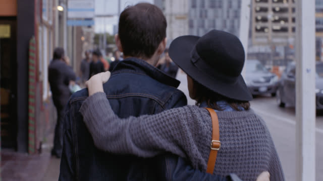 vidéos et rushes de young woman rubs boyfriend's back and puts her arm around him as they walk through downtown austin - passer le bras autour