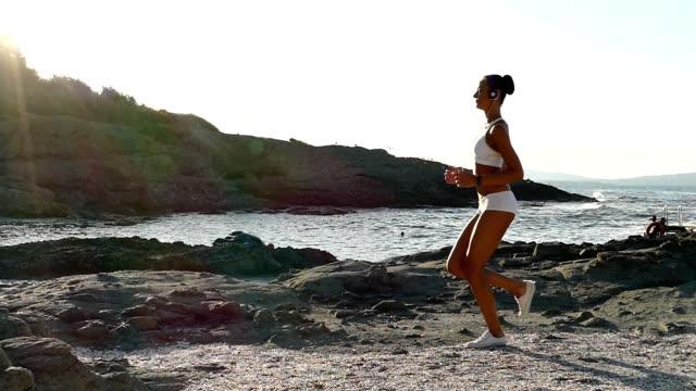 vídeos de stock e filmes b-roll de jovem mulher running na praia em câmara lenta - vista lateral