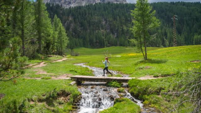 Junge Frau Läufer laufen auf einem Pfad auf einer Wiese über Bach