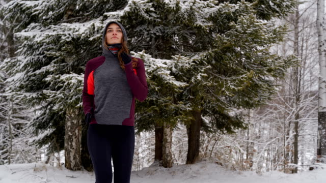 young  woman runner warming up and exercising before jogging in snow, outdoor sport and fitness concept - warm up exercise stock videos & royalty-free footage