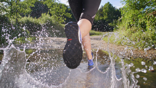 slo mo young woman running across a puddle - running shorts stock videos and b-roll footage