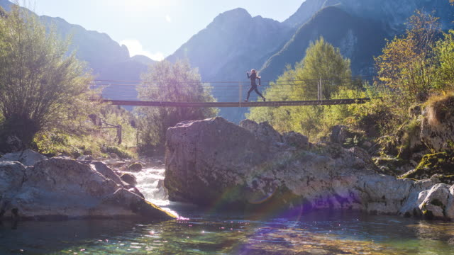 Young woman running across a suspension bridge over mountain stream