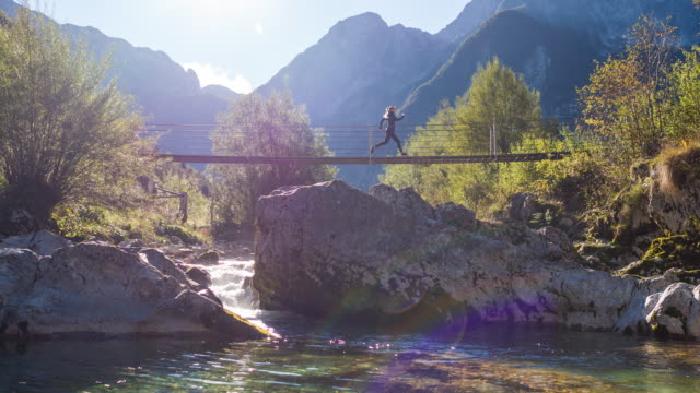 young woman running across a suspension bridge over mountain stream - competitive sport stock videos & royalty-free footage