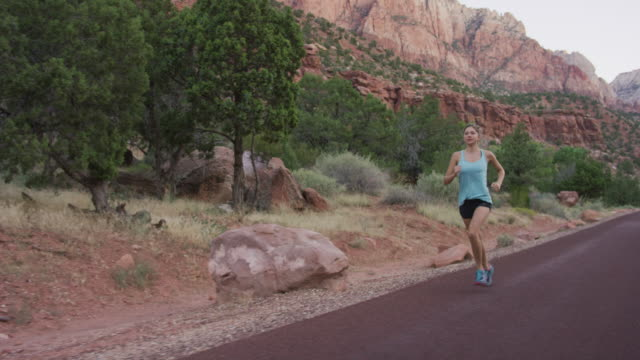 young woman running along road through canyons - canyon stock videos and b-roll footage