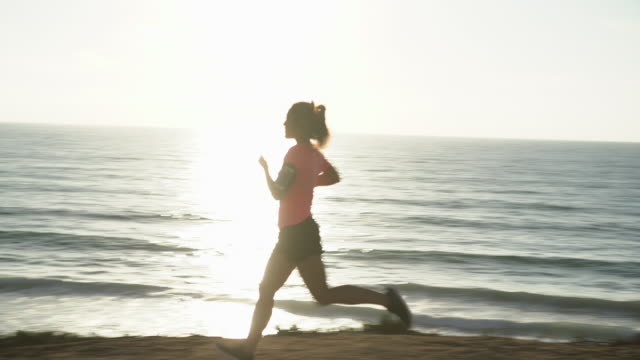 WS SM Young woman running along the ocean