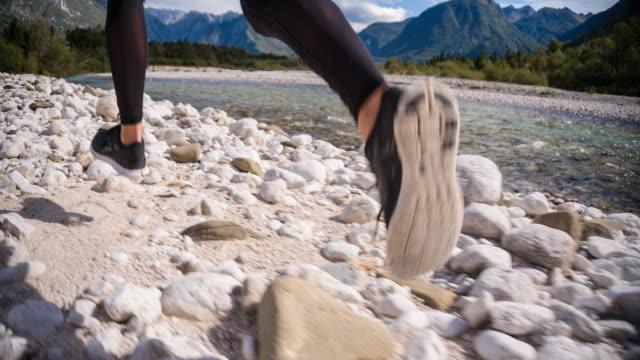 junge frau läuft neben einem fluss-strom - menschliches körperteil stock-videos und b-roll-filmmaterial