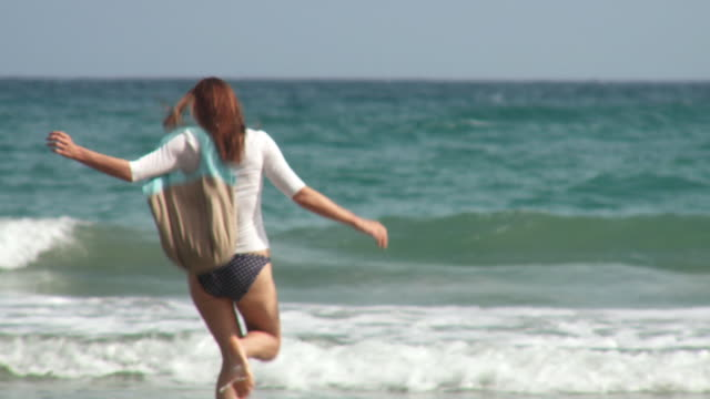 MS PAN Young woman running and jumping in surf with beach bag/ Scarborough, Tobago, Trinidad and Tobago
