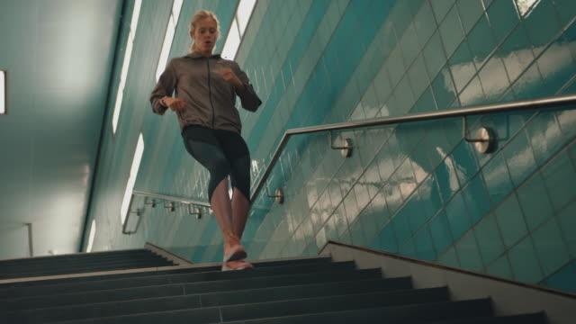 vídeos de stock e filmes b-roll de young woman running down on staircase at subway - corredor caraterística de construção