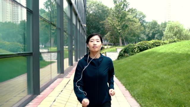 Young woman running facing camera