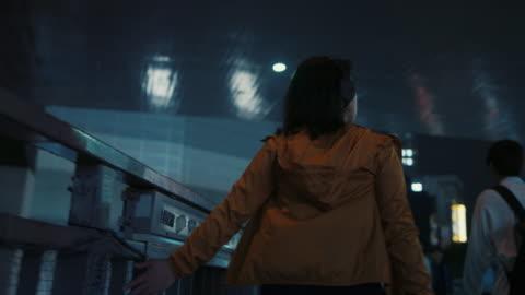 vídeos y material grabado en eventos de stock de young woman running hand along fence at night in tokyo, japan - resistencia