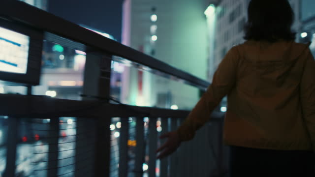 young woman running hand along fence at night in tokyo, japan - fence stock videos & royalty-free footage