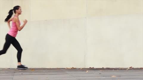 vídeos de stock e filmes b-roll de ws young woman running in an urban environment. - young women