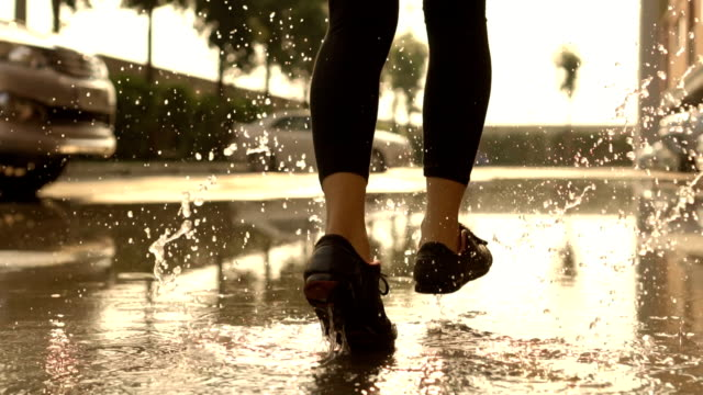 young woman running in parking slow motion. - puddle stock videos & royalty-free footage