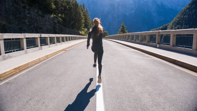 young woman running in the middle of a road - running stock videos & royalty-free footage