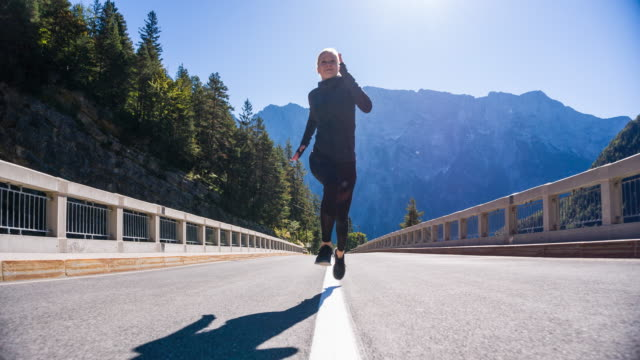 Young woman running in the middle of road toward camera
