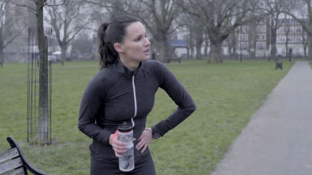 a young woman running in the park in winter. - approaching stock videos & royalty-free footage