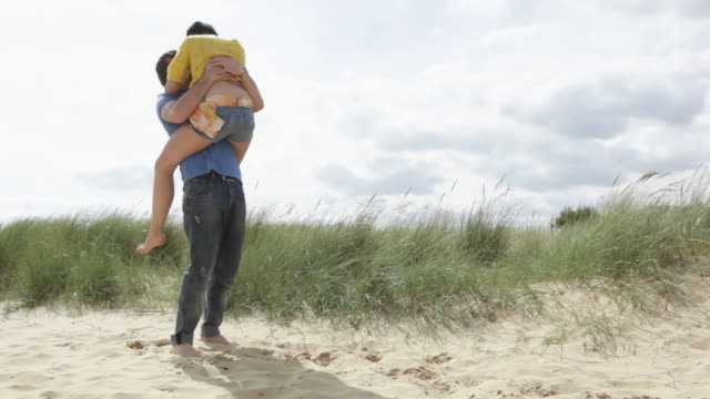 Young woman running into arms of boyfriend at beach