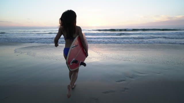 WS SM TS Young woman running into the water with her surfboard